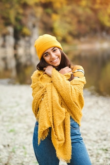 Beautiful woman enjoing autumn day. beauty and fashion. autumn fashion and lifestyle. pretty woman wearing warm autumn clothes, hat and yellow scarf. autumn mood. fashionable woman outdoors.