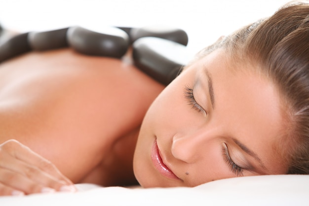 Beautiful woman enjoy spa with stones
