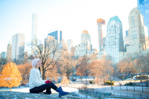Beautiful woman enjoy the view of ice-rink in central park and skyscrapers on manhattan in new york city