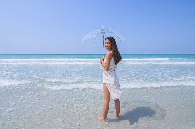 Beautiful woman enjoying the beach with an umbrella