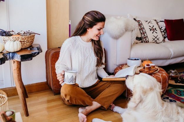 Beautiful woman enjoying a cup of coffee during healthy breakfast at home. writing on notebook. adorable golden retriever dog besides. lifestyle indoors