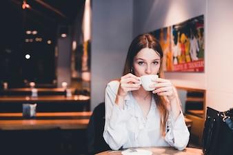 Beautiful woman enjoying drink in cafe