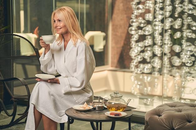 리조트 스파 호텔의 멋진 장소에 앉아있는 동안 그녀의 모닝 커피 또는 차를 즐기는 아름다운 여자