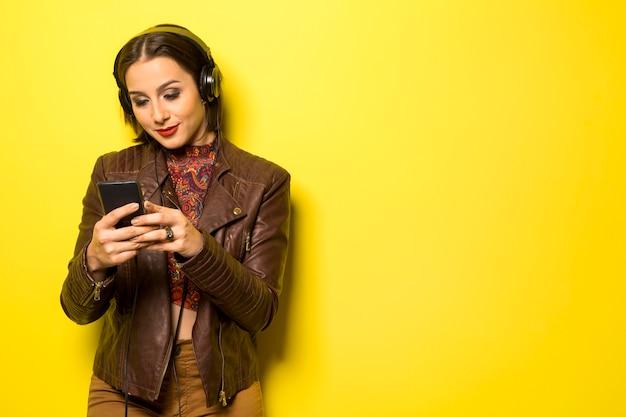 노란색 벽에 머리를 휴대폰으로 음악을 즐기는 아름다운 여자