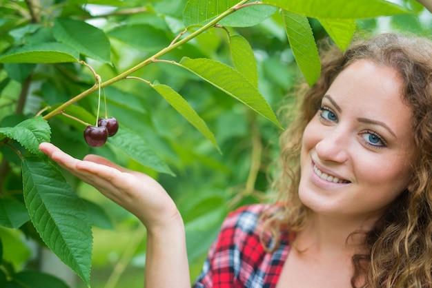 緑の果樹園でさくらんぼを拾うのを楽しんでいる美しい女性