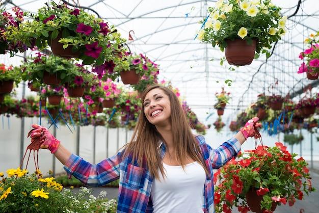 美しい女性は花と一緒に働くことを楽しんでいます