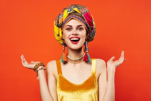 美しい女性の民族性色とりどりのヘッドスカーフメイクグラマー赤い背景。高品質の写真
