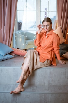Beautiful woman european appearance stylish bright clothes sits an interior studio against background white light window with various pillows holding round glasses with her hand, looking into camera.