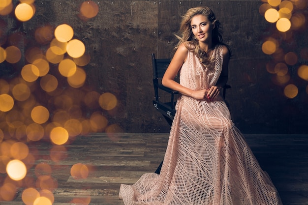 Beautiful woman in evening dress sitting in chair