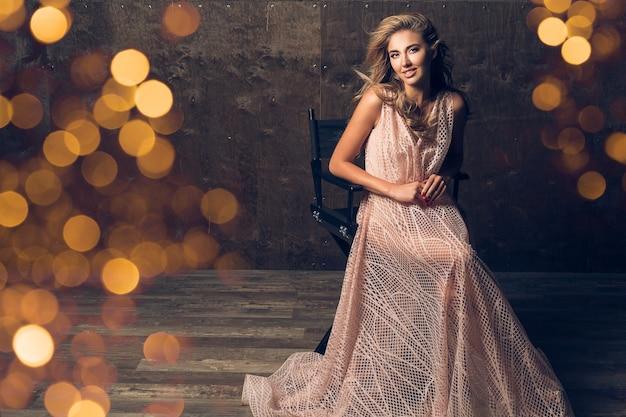 Beautiful woman in evening dress sitting in chair