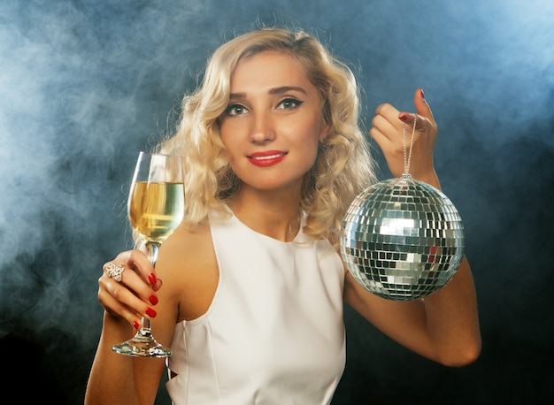 Beautiful woman in evening dress with wine and disco ball