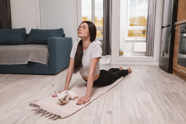彼女の犬と一緒に家で運動する美しい女性