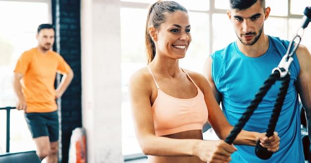 Красивая женщина тренируется в тренажерном зале с некоторой помощью личного тренера