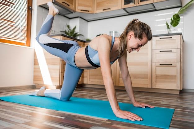 ヨガマットで運動している美しい女性
