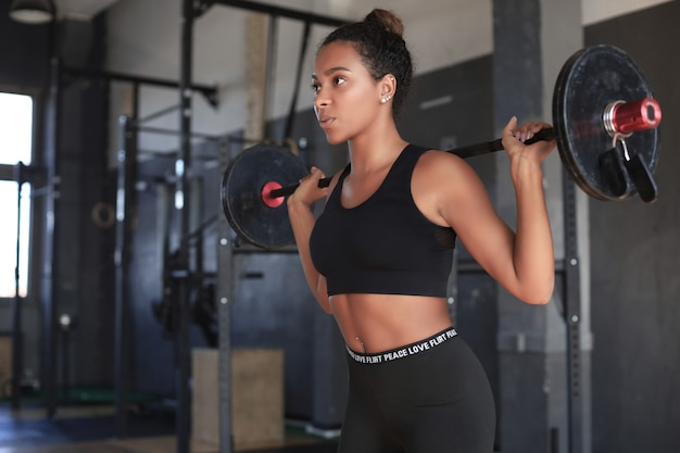 Beautiful woman exercising squatting with barbell at gym.