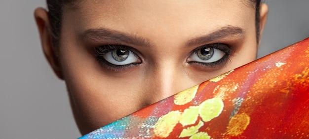 美しい女性の目と色のシルク布の横にある化粧