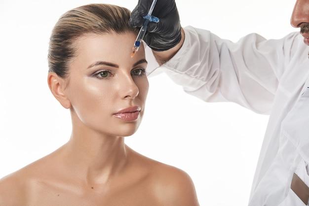 美しい女性の顔と医師の美容師または注射器で形成外科医の手