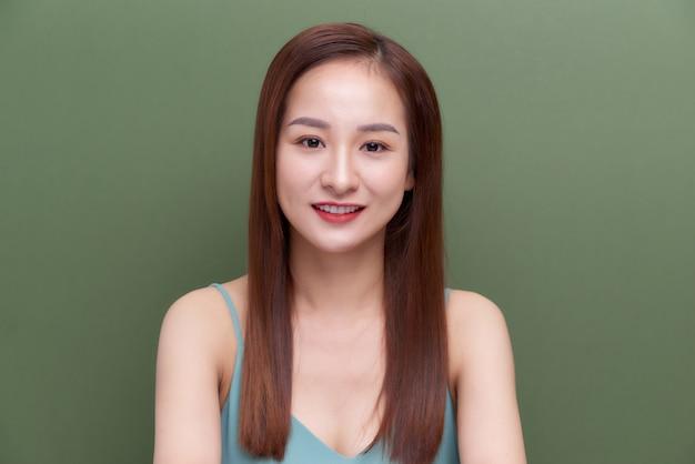 Красивая женщина лицо крупным планом портрет молодой студии на зеленом