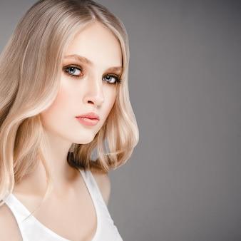 긴 금발 머리를 가진 아름 다운 여자 얼굴 초상화 뷰티 스킨 케어 개념. 회색 배경 위에 아름다운 헤어스타일을 한 패션 뷰티 모델