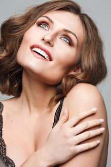 Красивое лицо женщины. идеальная зубастая улыбка. портрет крупным планом кавказской молодой девушки. розовые губы, кожа, зубы. стильный роскошный яркий макияж. студийный снимок. счастливая позитивная девушка.