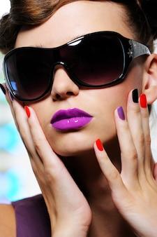 Fronte di bella donna con occhiali da sole alla moda neri e labbra viola luminose