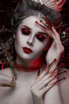 Beautiful woman face with creative fashion art makeup and with long red nails