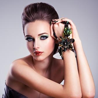 패션 녹색 메이크업과 보석 손에 아름 다운 여자 얼굴
