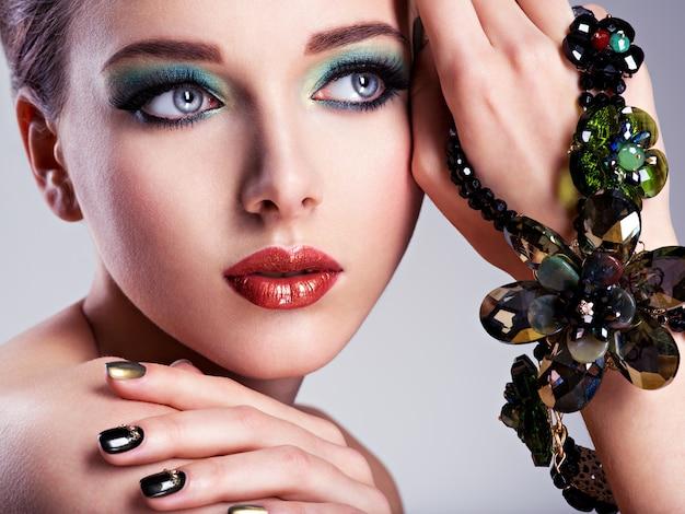 Bella donna faccia con moda verde trucco e gioielli a portata di mano