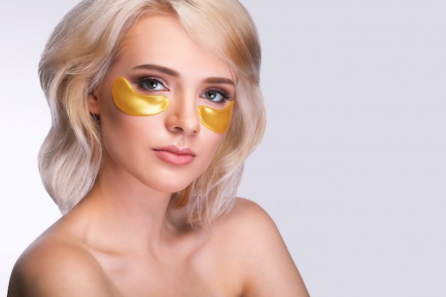 Beautiful woman face with gold hydrogel patches