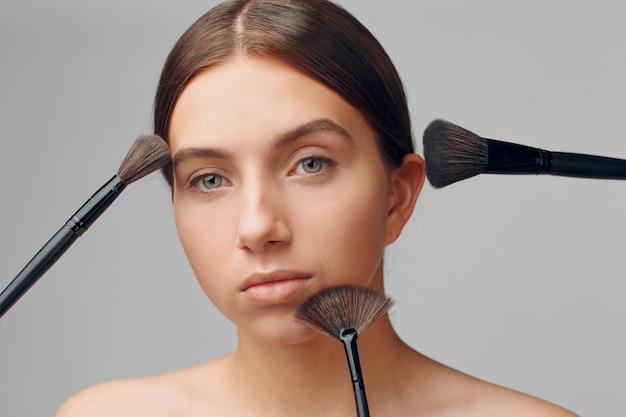 Красивая женщина лицо с естественным макияжем. рука мастера макияжа с кистью. юная красавица модель женского пола. макияж в процессе.