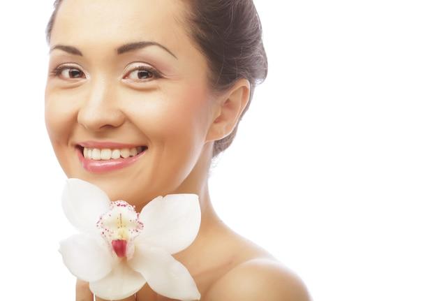 Лицо красивой женщины с цветком орхидеи