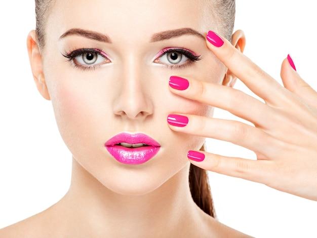 Fronte di bella donna con trucco rosa di occhi e unghie. ritratto di modello di moda glamour