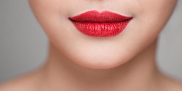 Лицо красивой женщины с красной помадой на пухлых полных сексуальных губах