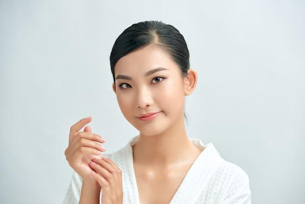 スキンケア、化粧品、美容衛生、化粧、保湿、白い背景で隔離の笑顔で美しい女性の顔