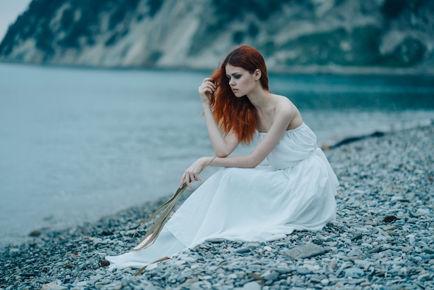 Beautiful woman in a fairy-tale look by the sea, a gentle fairy-tale look, white dress