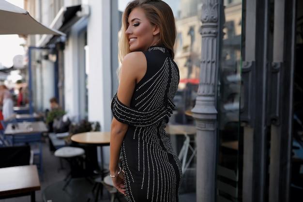 Beautiful woman in fancy dress, walking down the street, fashion, beauty, makeup, evening dress, smiling girl, posing model, luxury wearing, accessories, blonde, volume hair, lipstick, eyes, perfect
