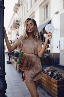 Bella donna in costume, camminando per strada, moda, bellezza, trucco, abito da sera, ragazza sorridente, modella in posa, abbigliamento di lusso, accessori, bionda, capelli voluminosi, rossetto, occhi, perfetti
