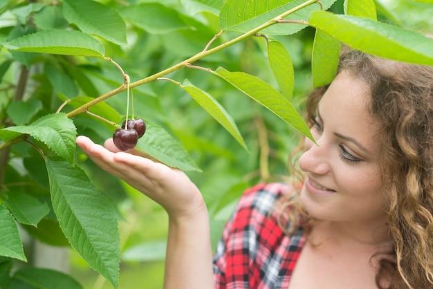 녹색 과수원에서 체리 과일을 들고 아름 다운 여자 농부