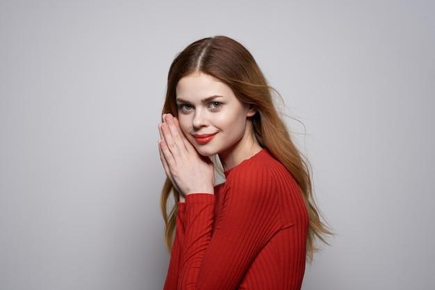 美しい女性のファッションの髪型赤いセーターモデルスタジオ