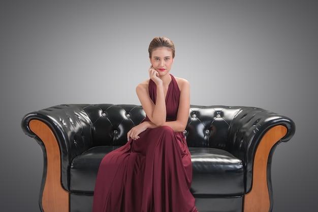 Красивая женщина модель модель сидит и позирует на диване