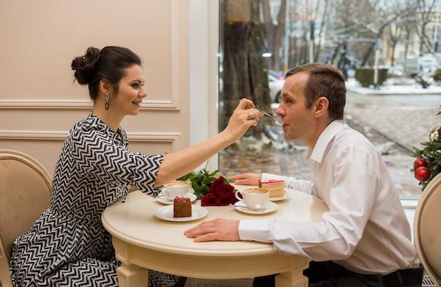 Красивая женщина кормит мужчину ложкой за столом в кафе