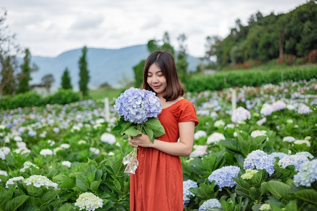 Beautiful woman feeling happy and relax at the hydrangeas flowers garden.