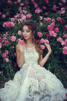 Beautiful woman in a floral park, garden roses. makeup, hair, a wreath of roses. long wedding dress. woman in boho style