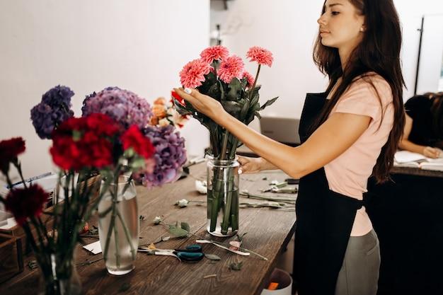검은 앞치마를 입은 아름다운 여성 꽃집은 꽃병에 있는 분홍색 국화를 만집니다.
