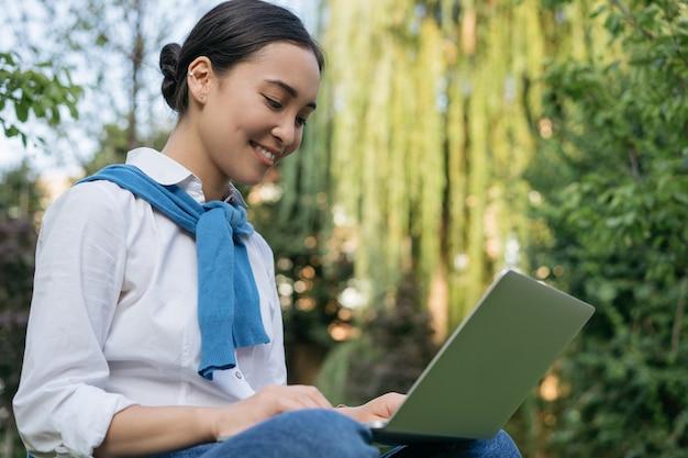 Beautiful woman freelancer using laptop, working, typing, searching information, sitting in park