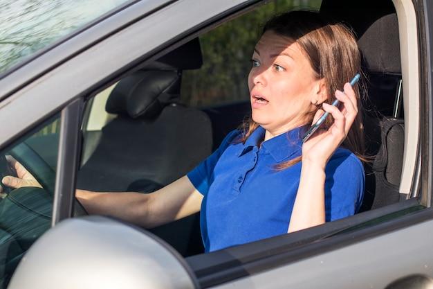Красивая женщина, напуганная испуганная девушка, водитель, молодая потрясенная леди, собирающаяся иметь дорожное происшествие, ведущий автомобиль, держащий в руке, говорящий по мобильному телефону на дороге отстегивается ремнем безопасности