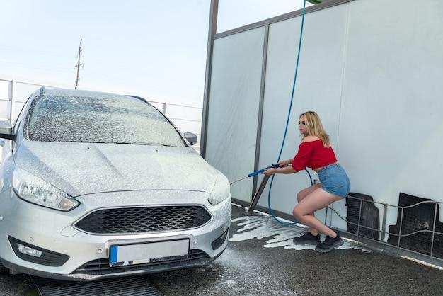 Красивая женщина из шланга высокого давления наносит мыльную пену на свою машину