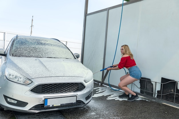 Beautiful woman from a high-pressure hose applies soap foam on her car