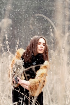 Beautiful woman in a fur coat with an owl on hand
