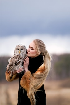 Beautiful woman in a fur coat with an owl on his arm. blonde with long hair in nature holding a owl